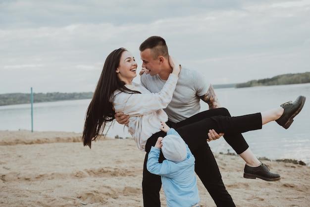Giovane famiglia felice che si diverte sulla sabbia sulla spiaggia in estate