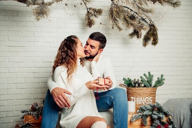 Giovane famiglia felice seduto in un abbraccio con un regalo nelle loro mani in un interno di casa invernale.