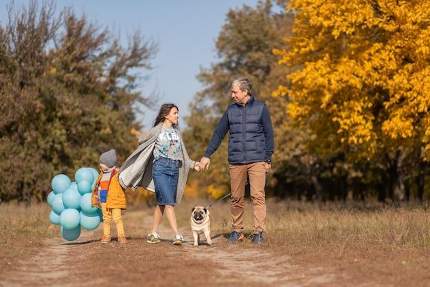 Una giovane famiglia felice con un bambino piccolo e un cane si diverte a trascorrere del tempo insieme per una passeggiata nel parco autunnale
