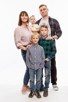 La giovane famiglia felice con tre bambini sta levandosi in piedi. amore e tenerezza.