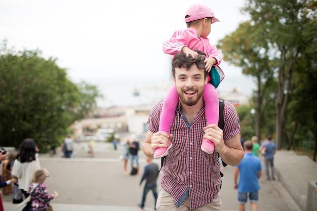 Il giovane padre felice tiene la ragazza del bambino sulle sue spalle e posa sulla macchina fotografica