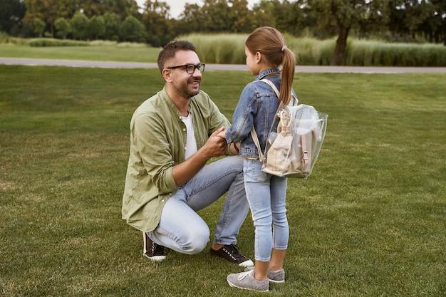 Giovane padre felice che tiene per mano la sua piccola figlia carina con lo zaino che parla con lei e