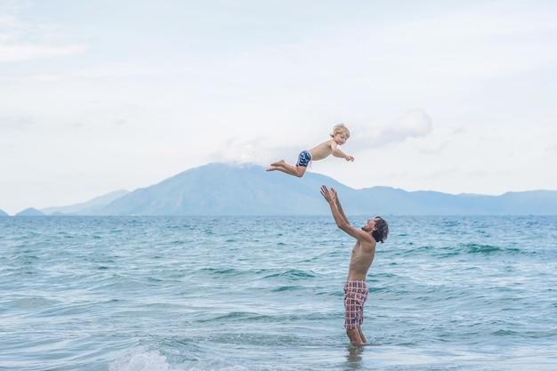Giovane padre felice che tiene in braccio il piccolo figlio mettendolo sulla spiaggia onde sabbia bagnata divertendosi con il bambino in costa al tramonto di estate.
