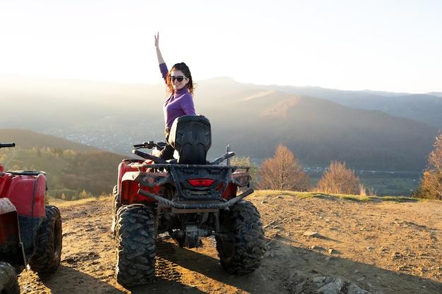 Giovane autista femminile felice che si gode un giro estremo su una moto quad atv in montagne autunnali al tramonto.