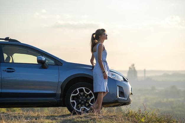 Giovane autista femminile felice che riposa vicino alla sua auto godendosi la vista del tramonto della natura estiva. destinazioni di viaggio e concetto di ricreazione.