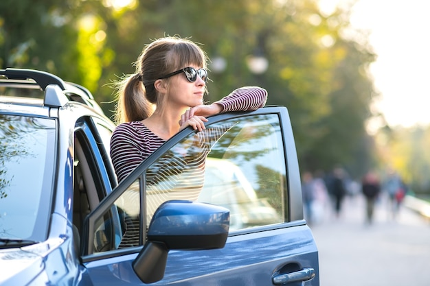 Giovane pilota femminile felice in piedi vicino alla sua auto su una strada cittadina in estate. destinazioni di viaggio e concetto di trasporto.