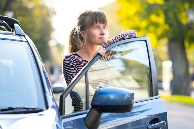 Giovane autista femminile felice in piedi vicino alla sua auto su una strada cittadina in estate. destinazioni di viaggio e concetto di trasporto.