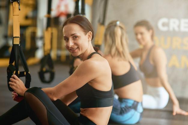 Giovane donna felice di forma fisica che si siede sulla stuoia di yoga e sorride alla macchina fotografica mentre si allena trx in palestra, messa a fuoco selettiva. sport, benessere e stile di vita sano