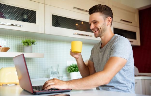Il giovane uomo libero professionista felice beve la tazza di tè o di caffè mentre lavora al computer portatile a casa