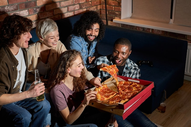 Amici giovani e felici che mangiano pizza e guardano film o serie tv a casa, gli studenti americani si godono il tempo libero dopo le lezioni, riposandosi dopo una dura settimana
