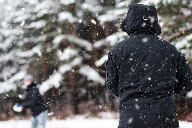 Giovani amici felici che godono lanciando palle di neve