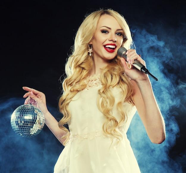 Giovane ragazza felice che canta nel microfono alla festa Foto Premium