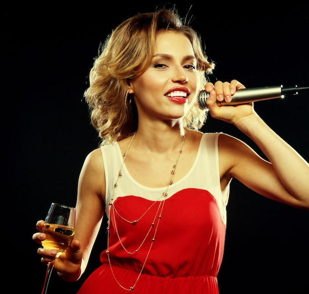 Giovane ragazza felice che canta nel microfono alla festa