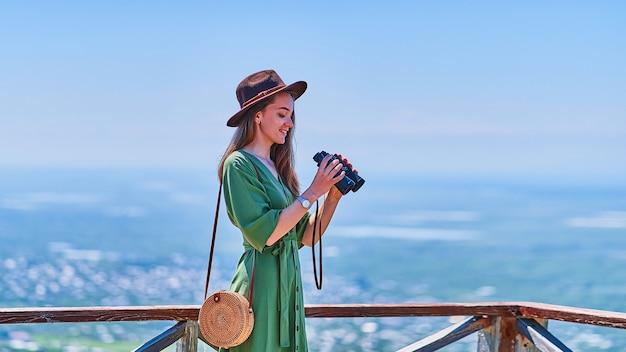 Giovane viaggiatrice felice che indossa un cappello con un binocolo durante il viaggio del fine settimana di vacanza in una luminosa giornata di sole