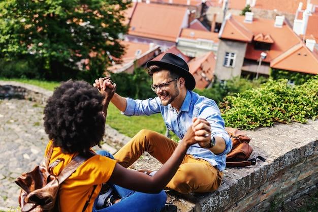 Coppia giovane hipster felice seduti all'aperto in una parte vecchia della città, tenendosi per mano e flirtando.