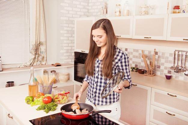Giovane casalinga felice che frigge carne di pollo per cena