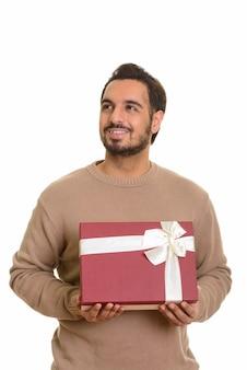 Giovane uomo indiano felice che tiene confezione regalo mentre si pensa