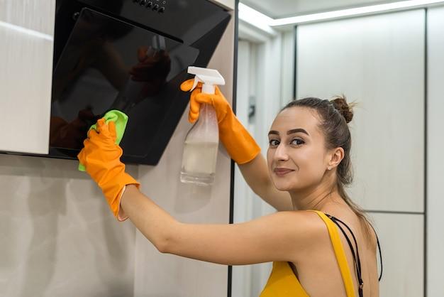 Giovane e felice signora in guanti protettivi che pulisce la sua cucina