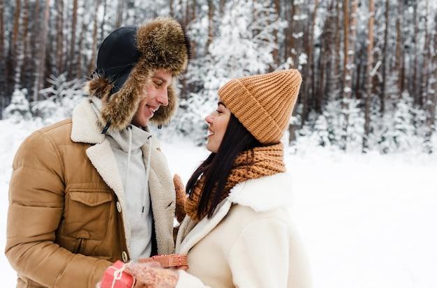 Una giovane, felice, amorevole coppia si abbraccia in una foresta innevata. buon fine settimana. san valentino.