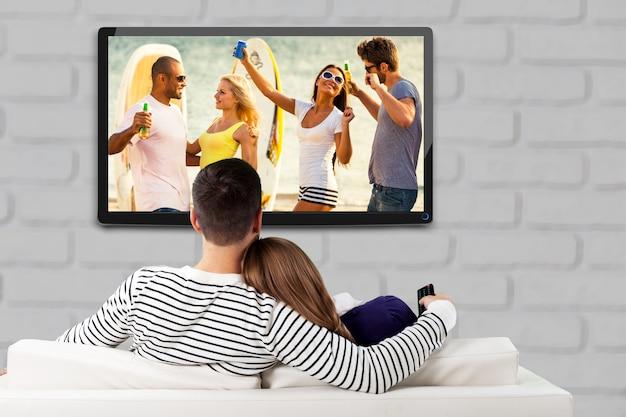Giovani coppie amorose felici che si siedono sul sofà all'interno e che guardano le foto sulla grande tv.