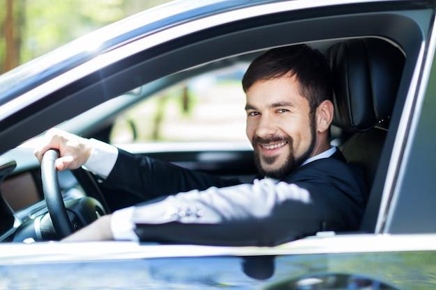 Giovane uomo felice in macchina sorridente - concetto di acquisto di auto