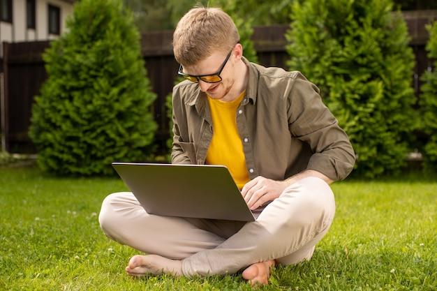 Giovane uomo felice in abbigliamento casual che riposa seduto sull'erba nel parco con il computer portatile in mano, ragazzo sorridente che apprende le lingue a distanza, guarda lo show televisivo di conferenza online, webinar aziendale, chiacchierando con gli amici