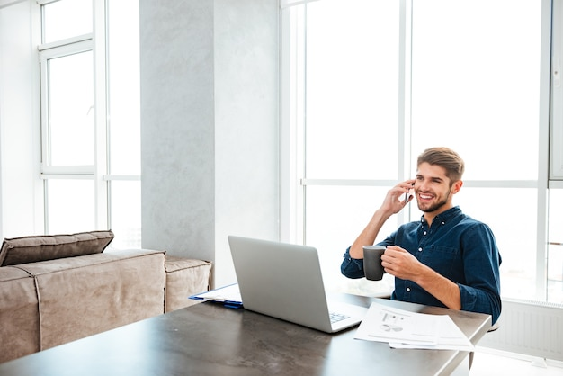 Giovane uomo felice che beve il tè e seduto vicino al tavolo con laptop e documenti mentre parla al suo telefono. guardando il laptop