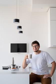 Giovane uomo felice che si gode la colazione a casa, pensando