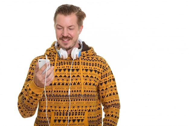 Giovane uomo felice che tiene telefono cellulare mentre indossa le cuffie al collo