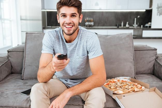 Giovane uomo felice che tiene il telecomando e premendo il pulsante mentre era seduto sul divano vicino alla pizza.