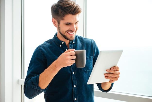 Giovane uomo felice che tiene compressa e bere caffè vicino alla finestra. guardando il tablet.