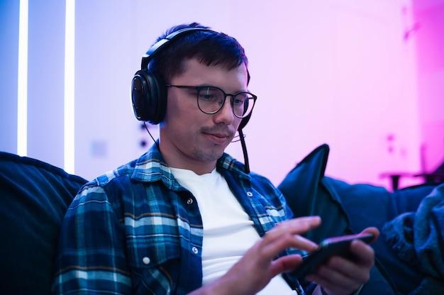 Giovane uomo felice che ascolta la musica con le cuffie e lo smartphone mentre vi rilassate sul divano.
