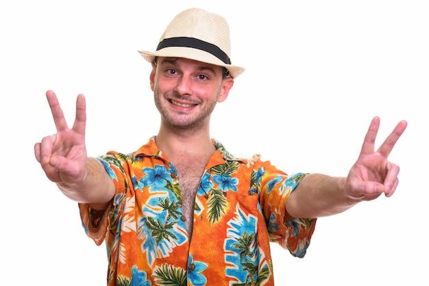 Giovane uomo felice che sorride mentre dà il segno di pace