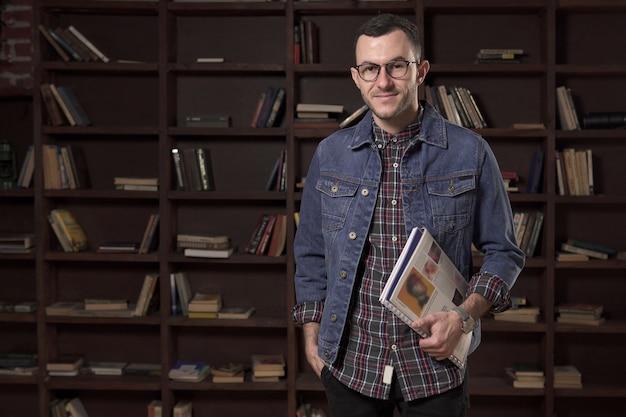 Giovane studente uomo felice in possesso di un libro di fronte allo scaffale