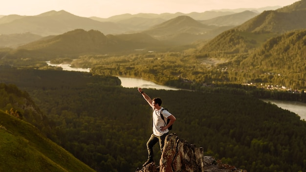 Un giovane uomo felice un turista con una mano sorridente alza la mano come un vincitore sullo sfondo di una valle di montagna e di un fiume al tramonto. concetto di viaggio alla natura e alle montagne