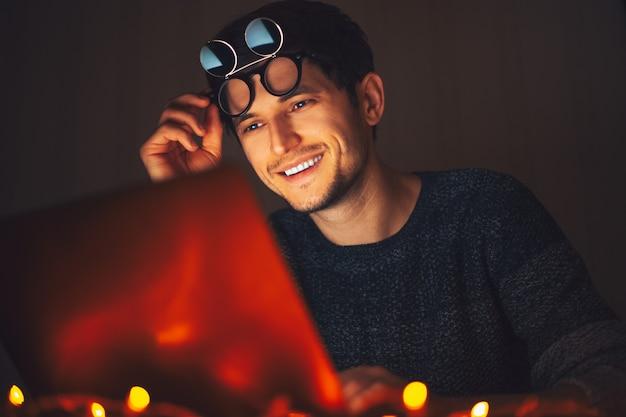 Giovane uomo felice che indossa occhiali rotondi, guardando nel computer portatile in camera oscura con ghirlande a casa.
