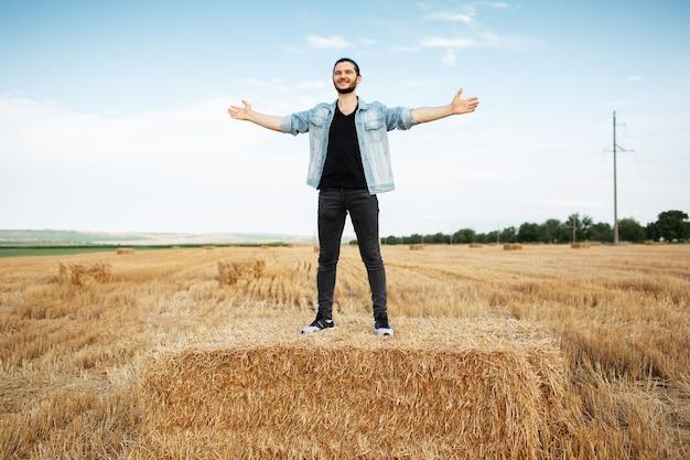 Giovane uomo felice con le mani in piedi su mucchi di fieno nel campo di grano.