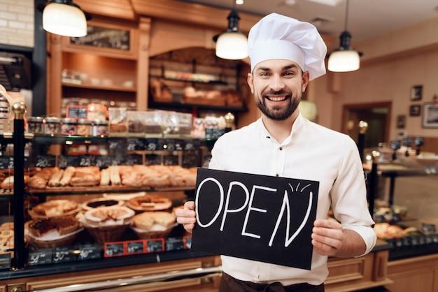 Giovane uomo felice con il segno aperto che sta nel forno.