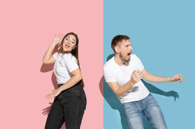 Giovane e felice uomo e donna in abiti casual sulla parete bicolore rosa e blu