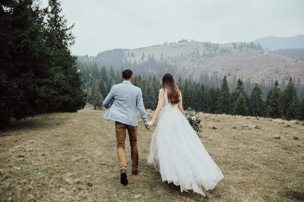 La giovane coppia sposata felice sta correndo nella foresta verde