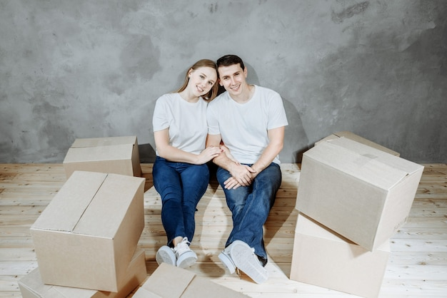 La giovane coppia sposata felice uomo e donna si siedono sul pavimento tra i contenitori per il trasloco nella loro nuova casa.