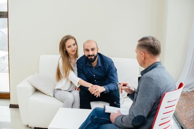 Una giovane coppia sposata felice di uomini e donne parla con uno psicologo durante una sessione di terapia. psicologia.