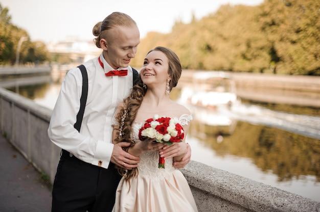 Giovane e coppia sposata felice che cammina lungo la riva del fiume in una calda giornata di sole
