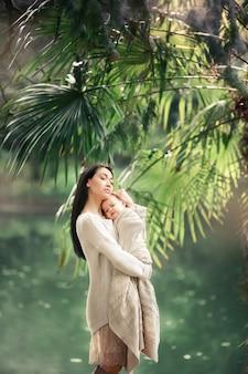 La giovane e madre felice si prende cura del suo giovane figlio e cammina lungo la riva del lago in estate nel parco