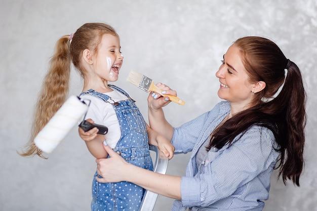 Una giovane madre felice sta accanto a sua figlia e tengono i rulli in mano e fanno le riparazioni a casa.