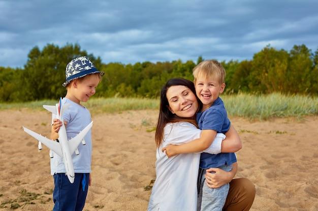 Una giovane madre felice con due ragazzi che giocano sulla sabbia vicino alla foresta, nelle mani di uno di loro un modello di aereo civile e un cappello in testa