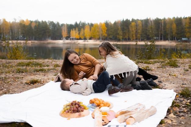 Una giovane madre felice con due bambini piccoli sta facendo un picnic nel parco in autunno con foglie colorate