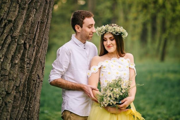 Giovani sposi felici che abbracciano in un parco di primavera, close-up