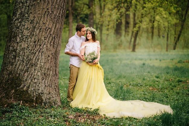 Giovani sposi felici che abbracciano in un parco di primavera