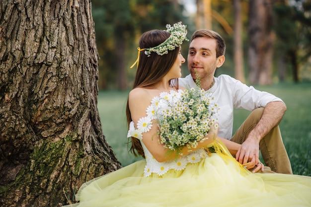 Giovani sposi felici che si siedono sull'erba vicino all'albero nel parco